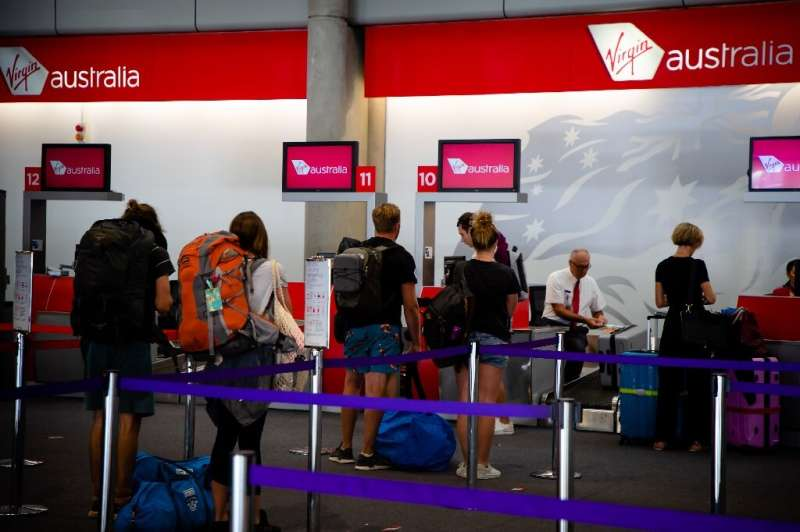 Passengers check-in at the Virgin Australia counter at Brisbane airport on April 21, 2020, after the carrier collapsed but said