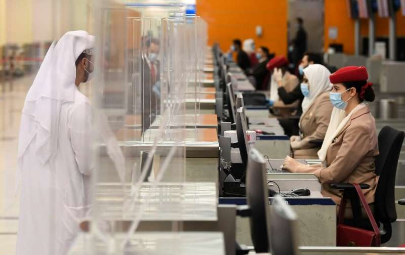 Passengers of an Emirates flight headed for the Australian city of Sydney check in at Dubai International Airport