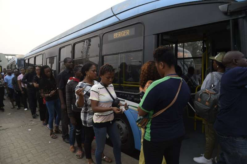 Passengers queue to board a bus provided by the government to offset the impact of the okada and keke ban. Passengers say fares