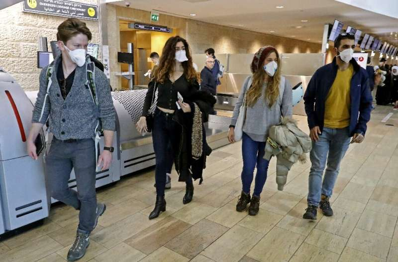 Passengers walk past check-in counters while wearing protective masks at Ben Gurion International Airport, near Tel Aviv