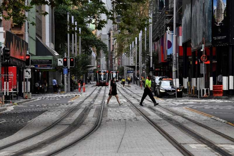 People cross a quiet road in central Sydney on March 25, 2020, as people stay away due to restrictions to stop the spread of the