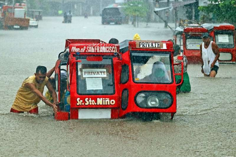 People push a half-submerged tricycle through a flooded street in Agusan del Sur province in Mindanao