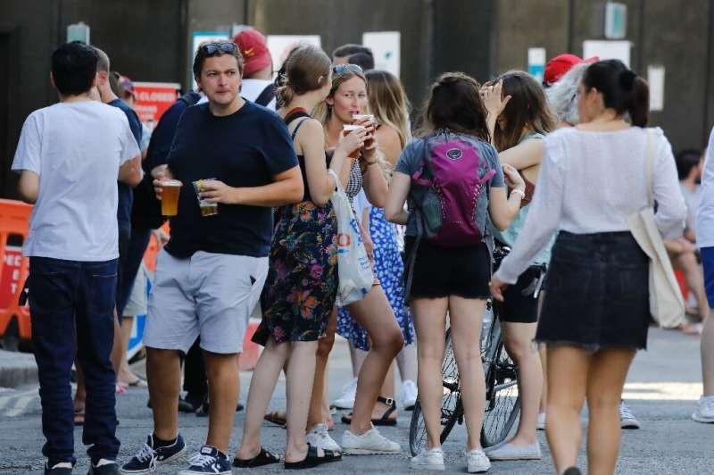 People relax with takeaway beer in plastic cups—and not much social distancing—at Borough Market in London