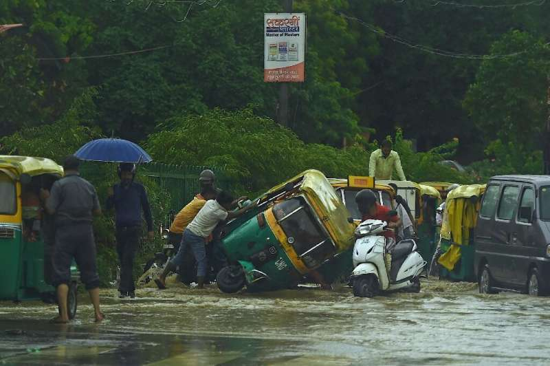 People try to pull an overturned auto rickshaw along a waterlogged road following monsoon rain in New Delhi