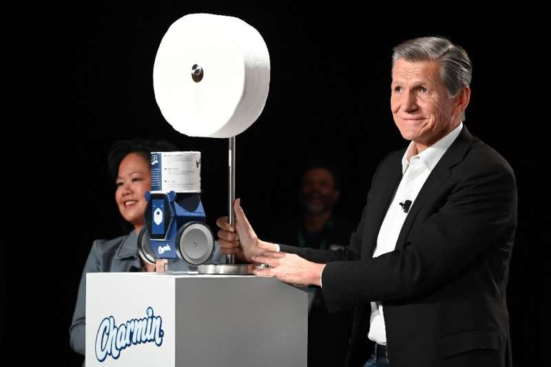 Procter & Gamble's chief brand officer displays a smartphone-activated robot that delivers toilet paper to the bathroom when