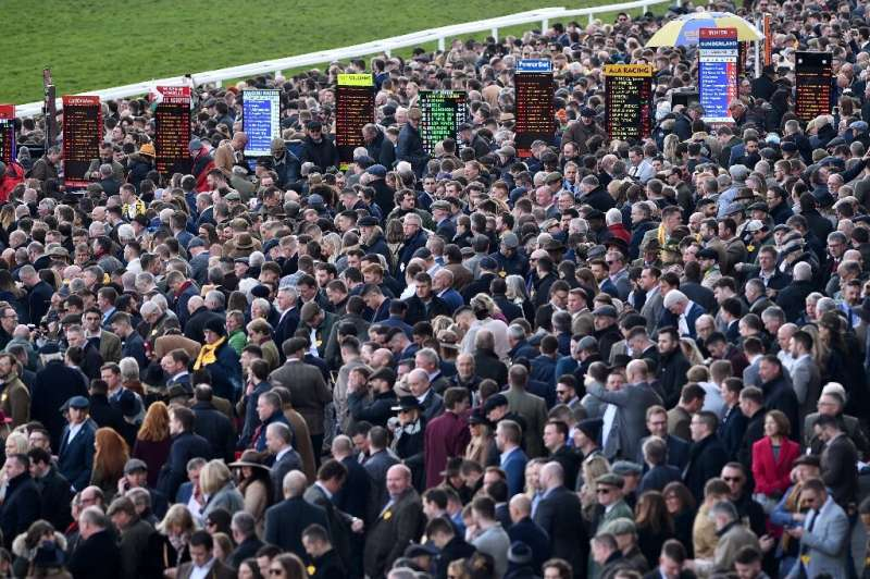Racegoers attend the final day of the Cheltenham Festival horse racing meeting in Gloucestershire, south-west England, on March