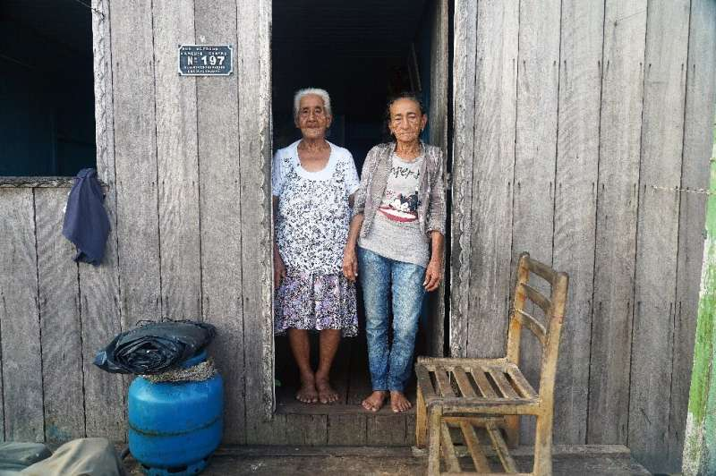 Raimunda Vianam (L), 88, and Maria Conceicao Braga, 76, pose in the town of Carauari where residents fear the reach and spread o