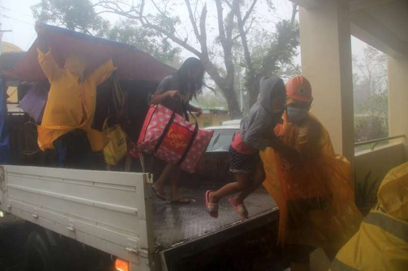 Rescuers help residents from a vehicle during the evacuation in Legazpi City, Albay province