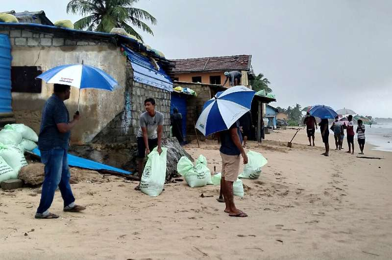 Residents prepare sand bags to protect their homes ahead of cyclone Burevi's landfall in Sri Lanka