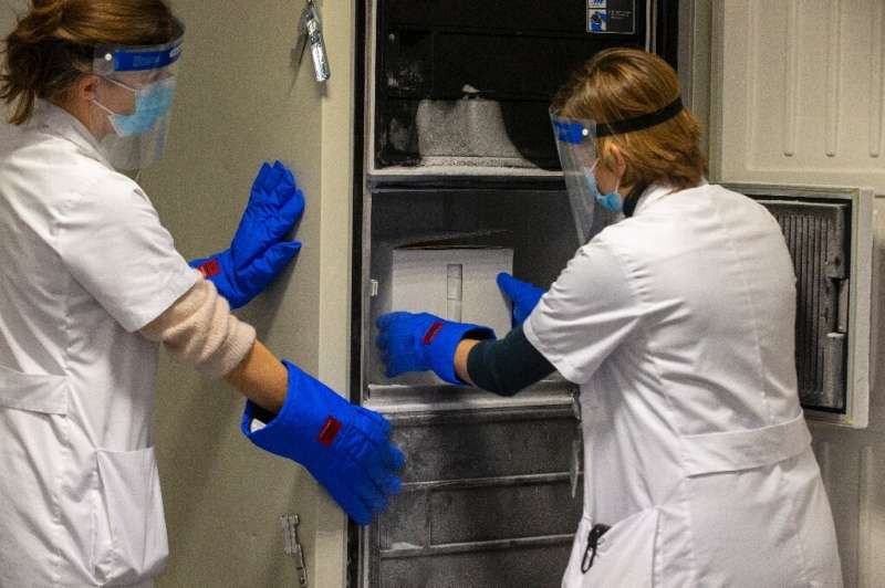 Staff at Belgium's UZ Leuven hospital pack a delivery of coronavirus vaccine into an ultra-low-temperature freezer