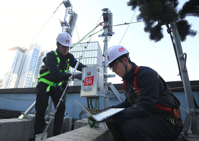 Technicians of South Korean telecom operator KT check an antenna for the 5G mobile network service in Seoul