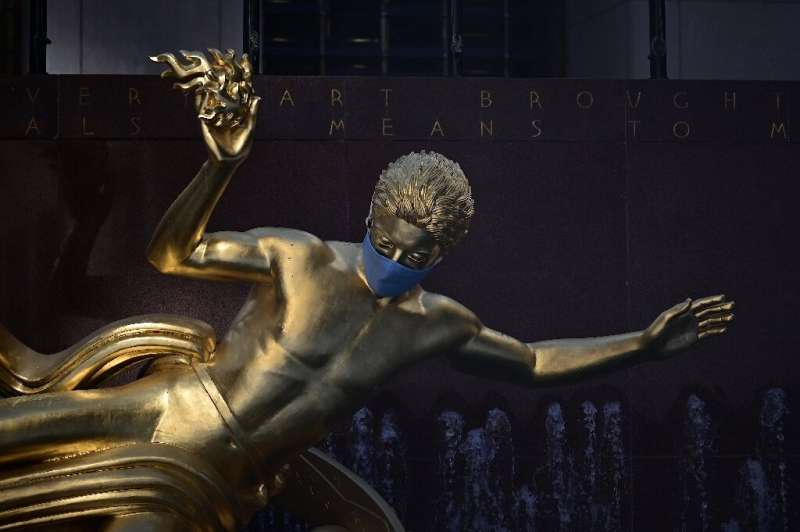 The sculpture of Prometheus adorned with a face mask is pictured at Rockefeller Center in Manhattan on June 24 in New York City