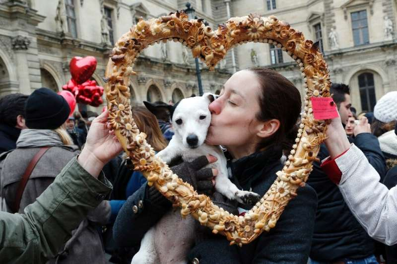True love: a woman and her Valentine's Day date pose behind a heart-shaped pastry during a February 14 Paris flash mob
