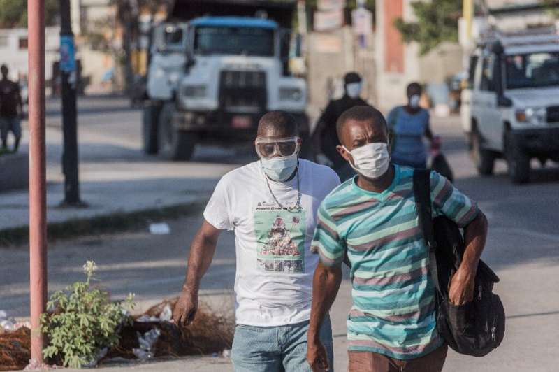 Two men wear masks as they walk in the streets of downtown Port-au-Prince on March 26, 2020. When the novel coronavirus first ap