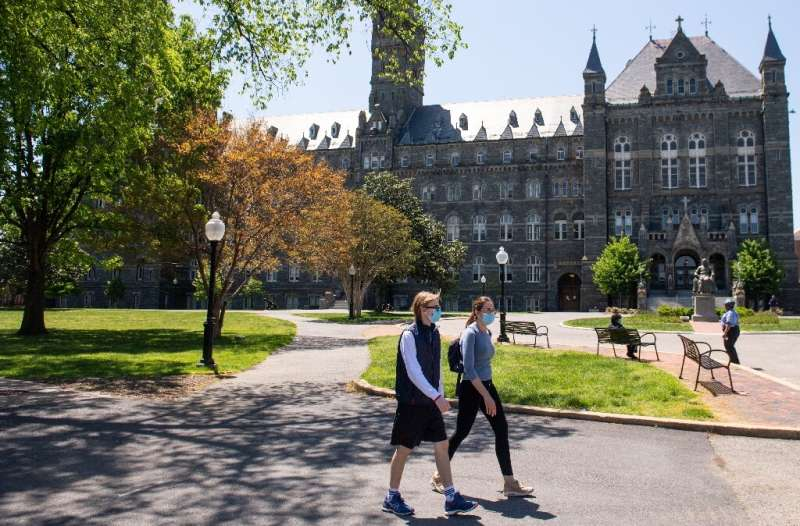 Two people wearing masks walk on the campus of Georgetown University in Washington