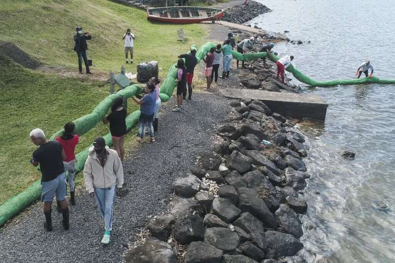 Volunteers carry a handmade oil barrier to block the leaked fuel from the MV Wakashio