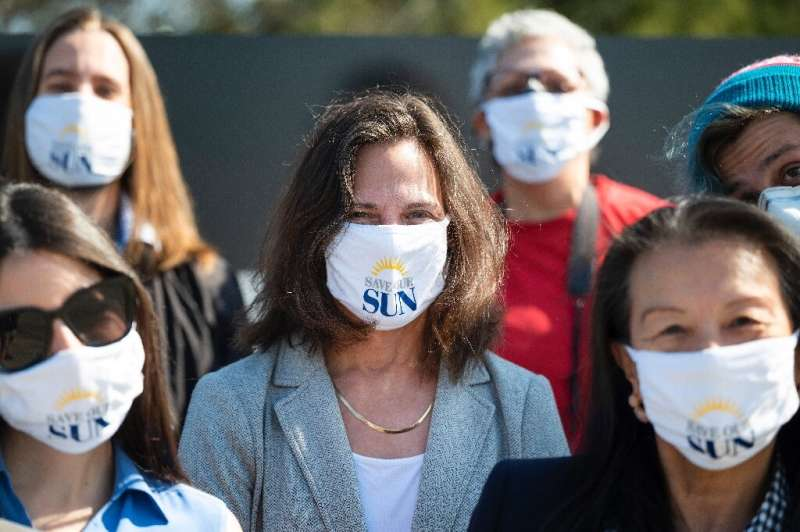 """Baltimore Sun reporter Liz Bowie (C) wears a """"Save Our Sun"""" facemask at a gathering with other journalists gathering M"""