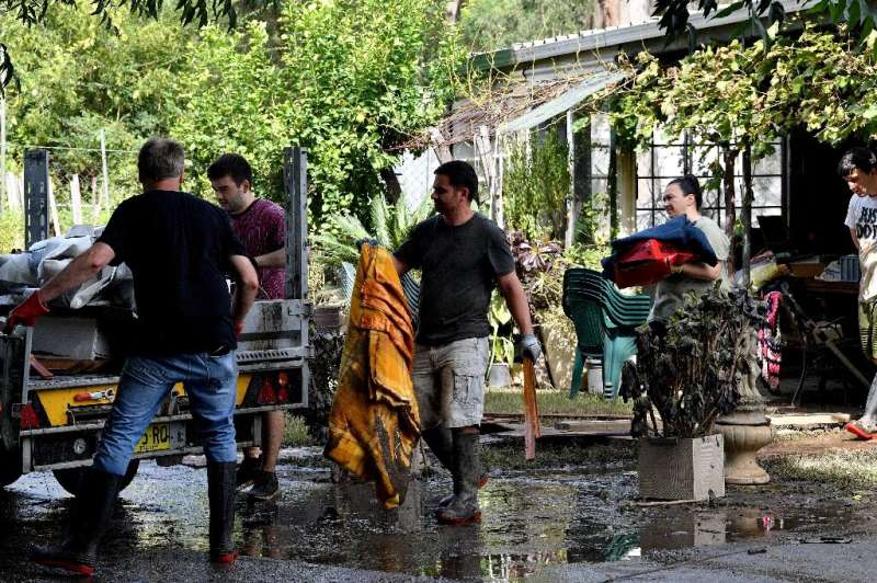 Residents clear out belongings from a home after floodwaters receded in Londonderry