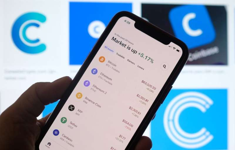 This illustration photo shows the Coinbase logo in the background as a person checks cryptocurrencies prizes on a smartphone in