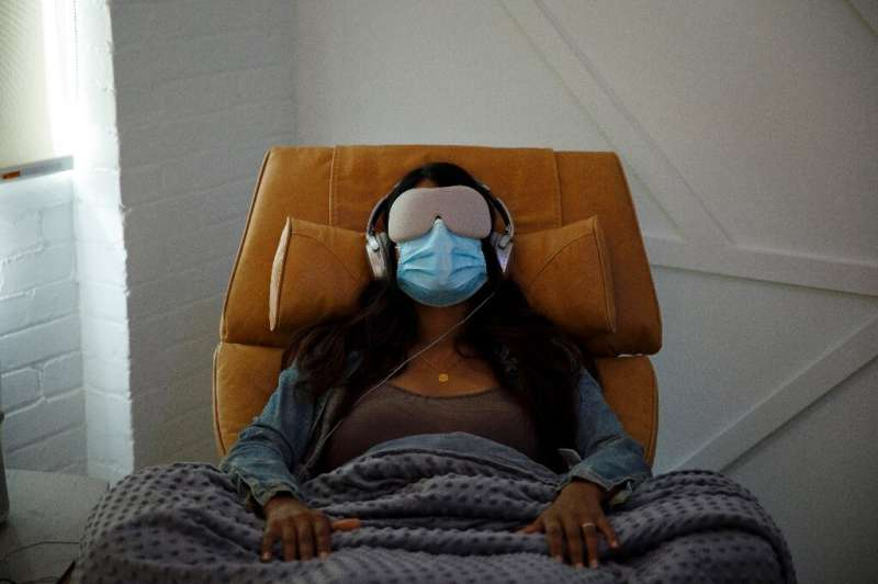 In this file photo taken on August 28, 2020, a woman demonstrates what a patient would experience in a therapy room at Field Tri
