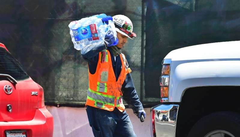 A construction worker carries bottled water in Los Angeles where an early heat wave is set to be in full swing