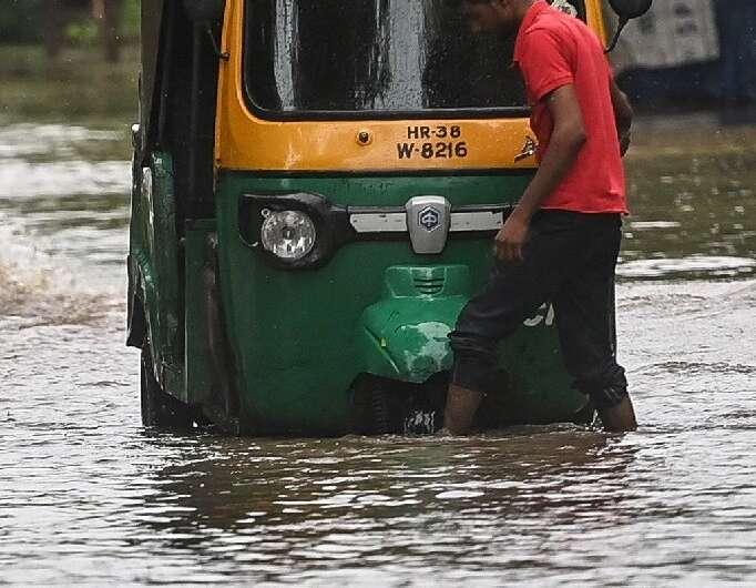 Un conductor revisa su vehículo después de que se atascara en el agua en Faridabad
