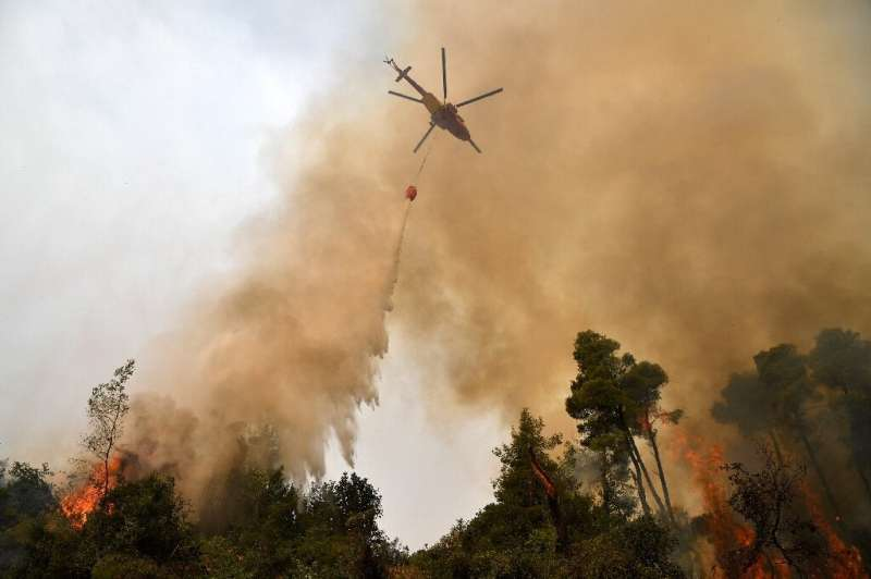 A helicopter pours water on a wildfire on August 5, 2021, near the village of Kechries in northern Evia