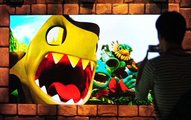 A large screen shows scenes from the game Skylander's Giants by Activision on the second day of the E3 videogame extravaganza in