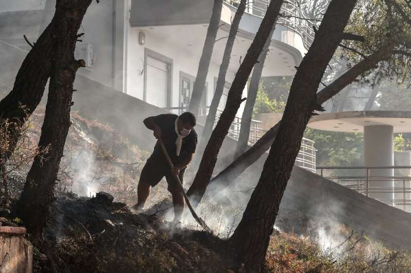 A local resident fights a fire flare-up north of Athens