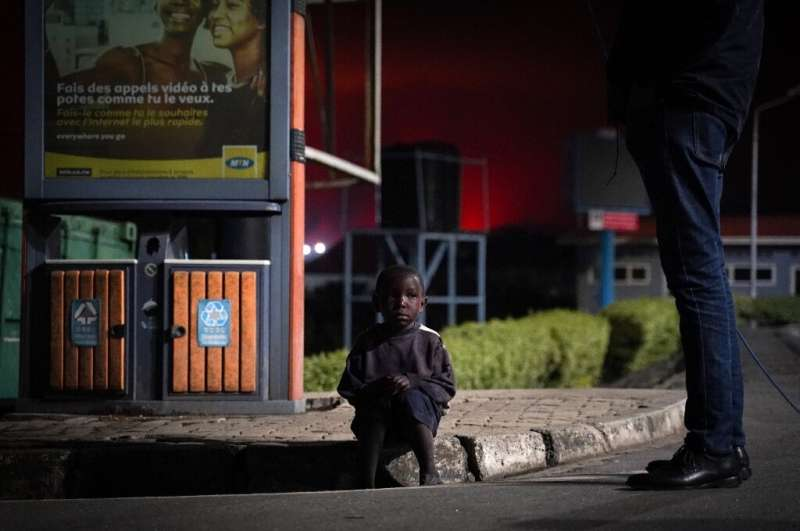 A lost child sits on a curb as people flee from Goma. UNICEF has said dozens of children have been separated from their parents