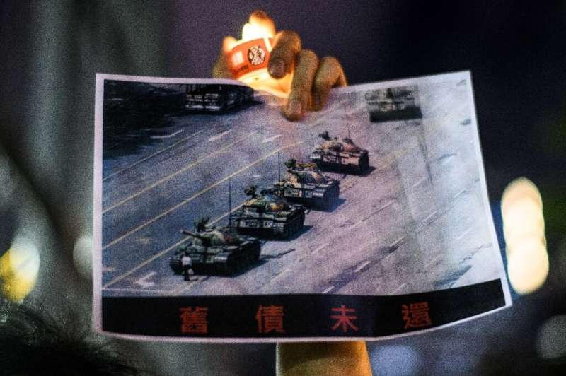 """A man holds a poster of the """"Tank Man"""" photo during a candlelit remembrance in Hong Kong's Victoria Park on June 4, 20"""