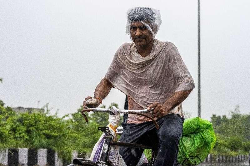 Un hombre anda en bicicleta por una calle durante las fuertes lluvias en Nueva Delhi.
