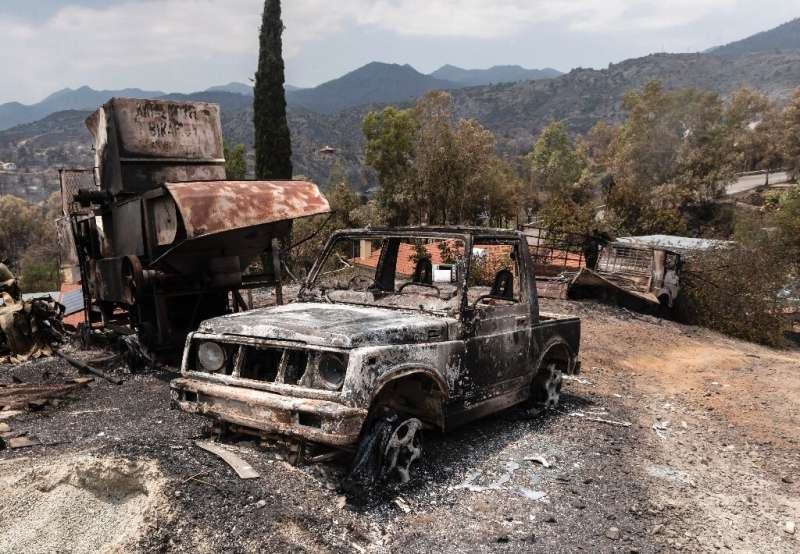 A picture taken on July 4, 2021 shows destroyed vehicles at Ora village on the southern slopes of the Troodos mountains in Cypru