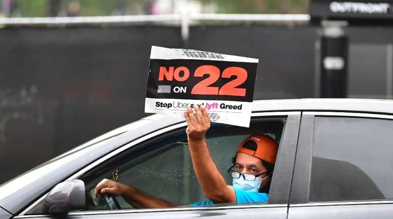 A rideshare driver demonstrates in Los Angeles against Proposition 22, which effectively overturned a state law requiring Uber,