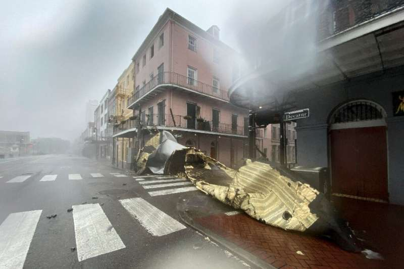 A section of a building's roof is blown off during rain and winds in the French Quarter of New Orleans on August 29, 2021