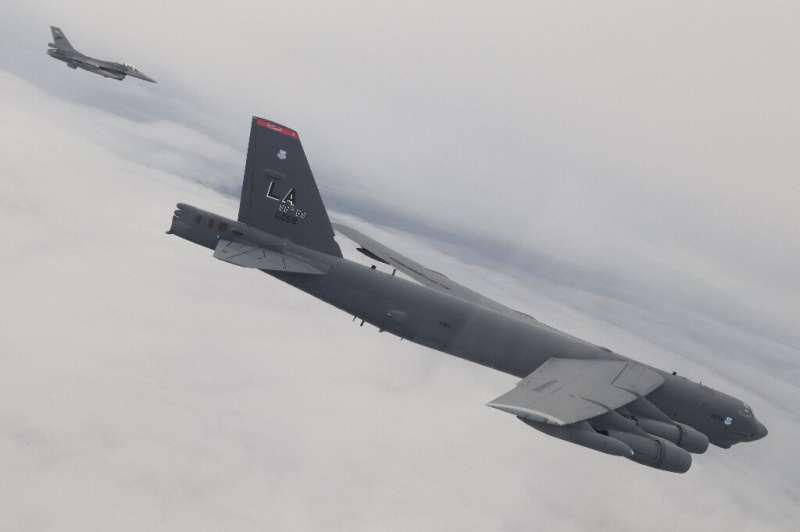 A US bomber B-52 bomber (R) accompanied by an Indonesian F-16 fighter jet (L) during a joint exercise over Sulawesi waters in In