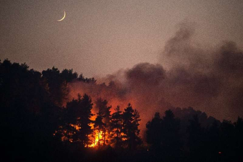 A wildfire blazes in the village of Gouves on Evia  island
