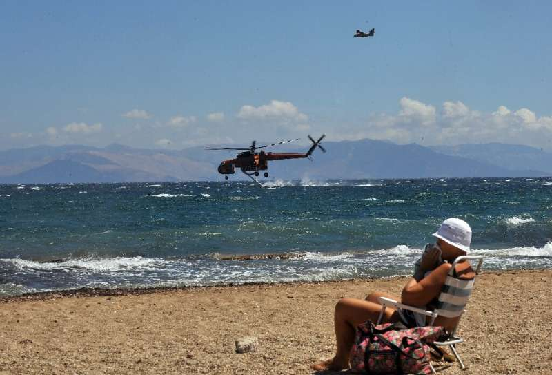 A woman sits on the beach while firefighting planes fill up with water in a resort of Nea Makri in eastern Athens on August 24,