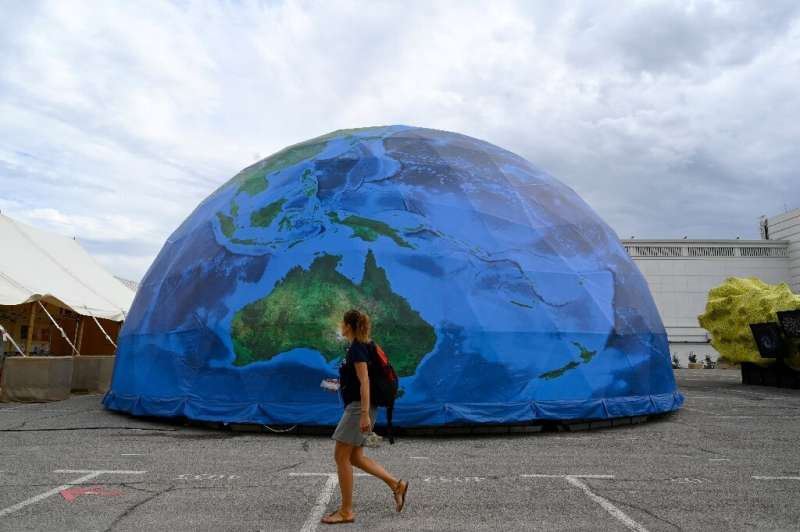 A woman walks past a partial replica of the Earth during the IUCN congress in Marseille, southern France