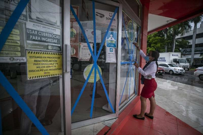 A worker places wooden boards on the windows of a supermarket to prevent damage caused by Pamela in Culiacan, state of Sinaloa,