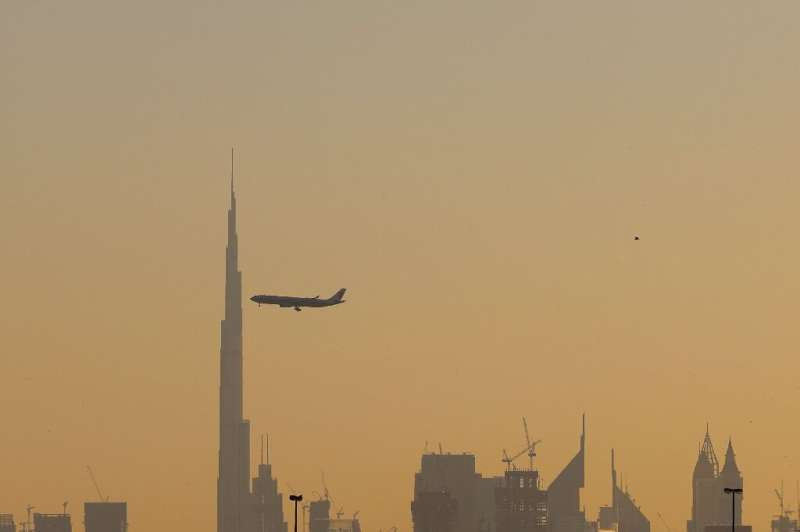 A commercial airplane flies past Burj Khalifa as it starts landing at Dubai international airport in the United Arab Emirates