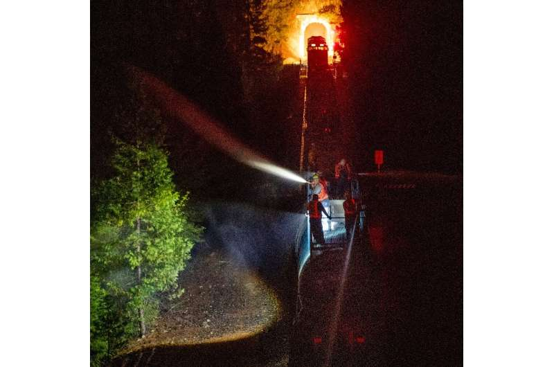Along steep slopes firefighters have used a train to spray the blaze