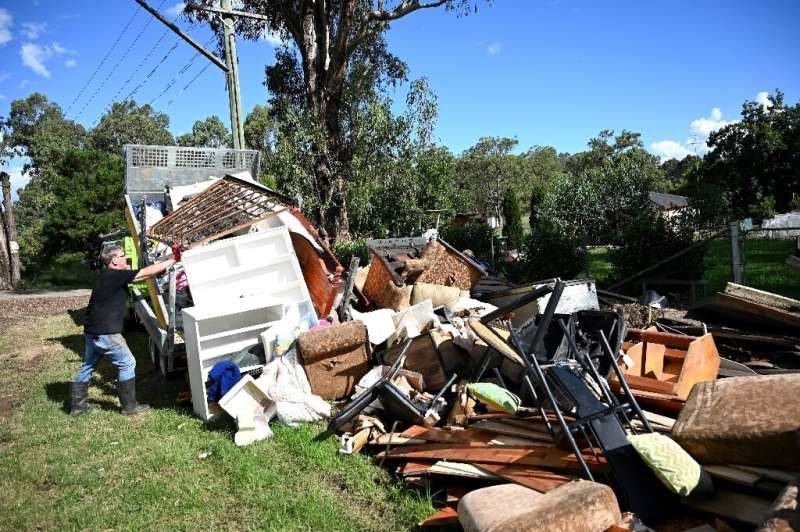 A man piles up damaged possessions outside his house in Londonderry, a suburb outside Sydney, as flood-stricken residents along