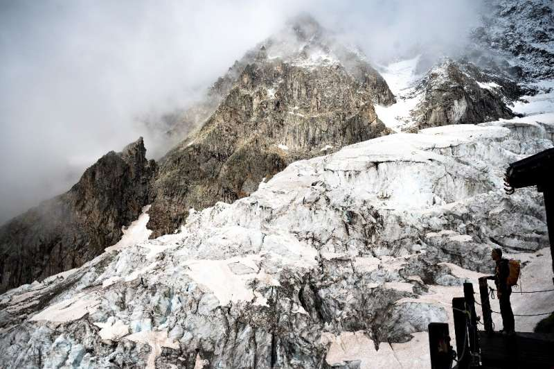 An alpinist stands on the balcony of the Boccalatte Hut on the Planpincieux Glacier in Courmayeur,  north-western Italy