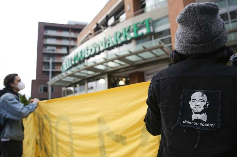An image of Amazon founder and CEO Jeff Bezos is pictured on a jacket as people rally rally outside a Whole Foods Market in soli