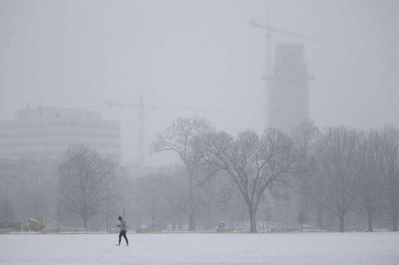 A person walks in Centennial Park as freezing rain falls in Nashville, Tennessee