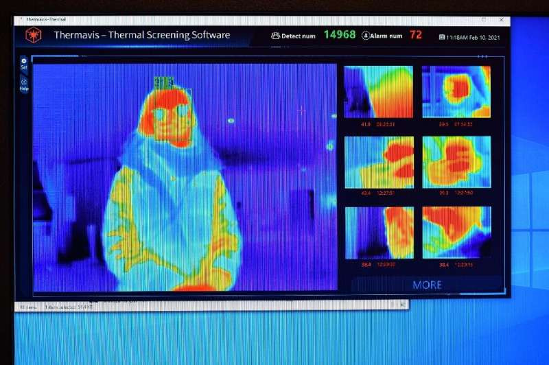 A thermal imaging camera are displayed on a screen as a person waits at the reception desk at the St Giles Hotel near Heathrow A