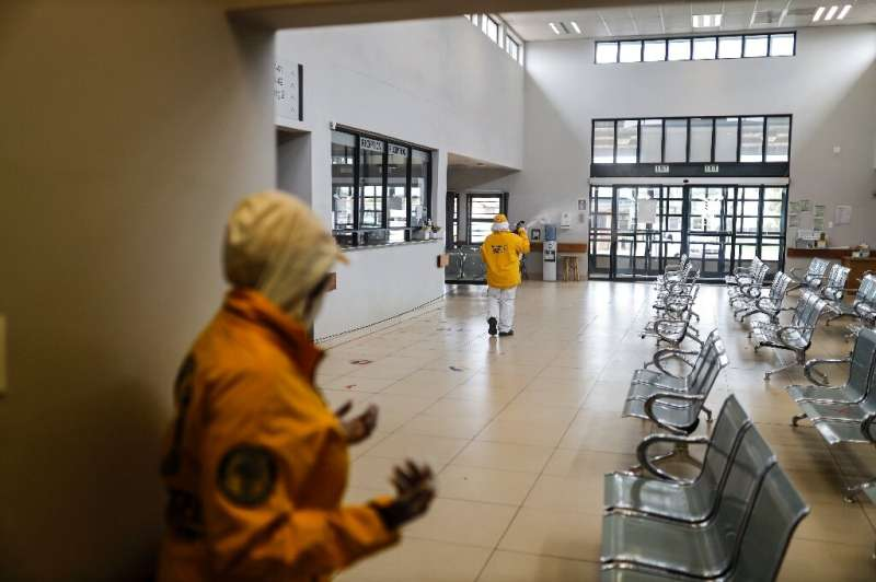 A volunteer sprays disinfectant during a deep cleaning operation inside the Villa Liza Clinic, in Ekurhuleni, South Africa, on J