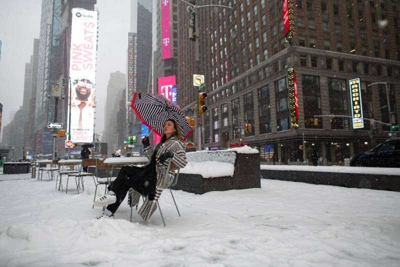 A woman poses in New York's Times Square during a winter storm on February 18, 2021