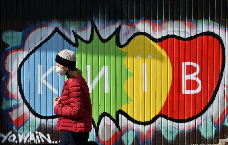 "A woman wearing a protective face mask walks in front of a graffiti reading ""Kiev"" during a warm spring day in the Ukr"